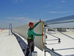 Worker installing a roof screen system on commercial roof.