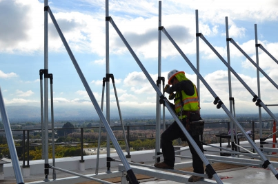 Worker installing panels on an equipment screen.