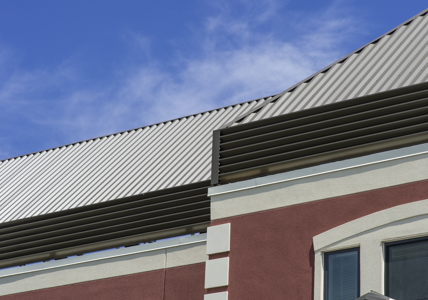 Aluminum Louvers With Vertically Ribbed Panels In Mansard Style Roof Screen