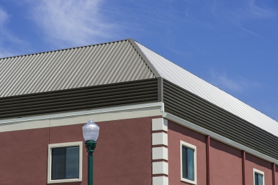 Continuous blade aluminum louvers around perimeter of mansard equipment screen.