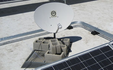 Satellite dish held down with concrete ballast blocks on commercial roof.